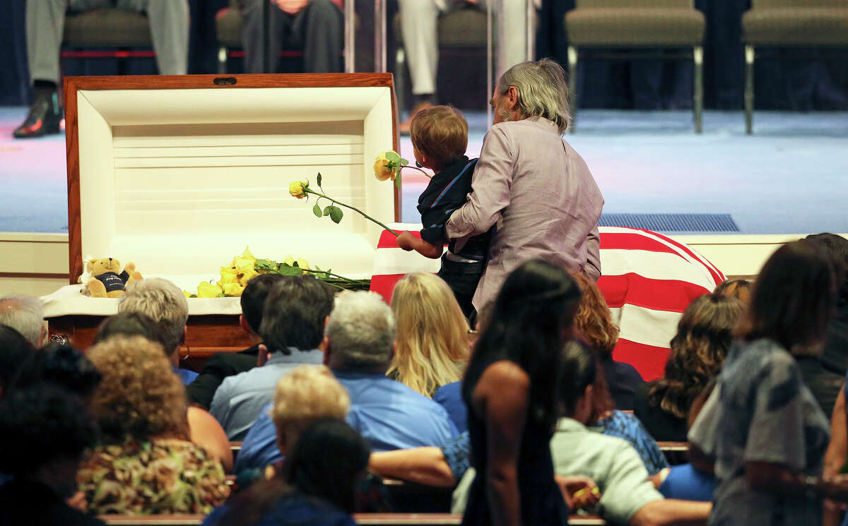 Family members place yellow roses on the casket at Cornerston Church during funeral services for Elmendorf Police Chief Michael A. Pimentel on September 2, 2014.