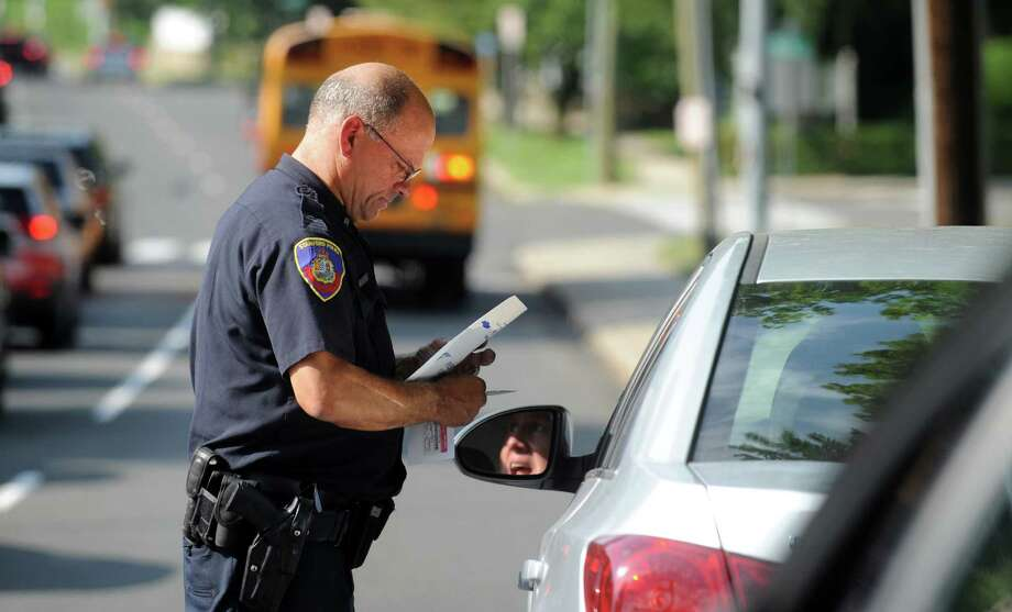 Stamford Police Officer Hugh Mullin gives a driver a citation Tuesday, Sept. 2, 2014, for failing to stop for a school bus along Bedford Street in Stamford, Conn. The police department is posting officers around the city to try to crack down on drivers passing stopped buses. Photo: Autumn Driscoll / Connecticut Post