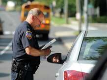 Stamford Police Officer Hugh Mullin gives a driver a citation Tuesday, Sept. 2, 2014, for failing to stop for a school bus along Bedford Street in Stamford, Conn. The police department is posting officers around the city to try to crack down on drivers passing stopped buses.