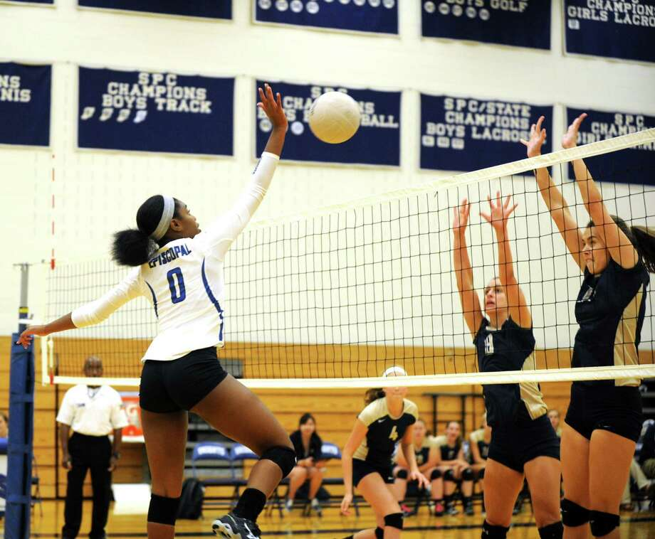 Second Baptist volleyball team visited Episcopal High School for a match, 8-12-2014.  Episcopal defeated Second Baptist, three games to one. Left, Episcopal's Naomi Aganekwu (0) hits the ball in an attempt to score over Second Baptist's Kendall Schroeder (9). Photo: Eddy Matchette, Freelance / Freelance