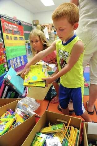 Jared Maroncelli, 5, of Wynantskill drops school supplies into boxes in Mrs. Ellen Moak's kindergarten class at Gardner-Dickinson School on Tuesday, Sept. 2, 2014 in North Greenbush, N.Y. Jared's older sister Isabella, 7, left, helps out. Parents brought their kindergarten students to drop off school supplies, meet their teachers and take a quick bus ride. (Lori Van Buren / Times Union) Photo: Lori Van Buren / 00028410A