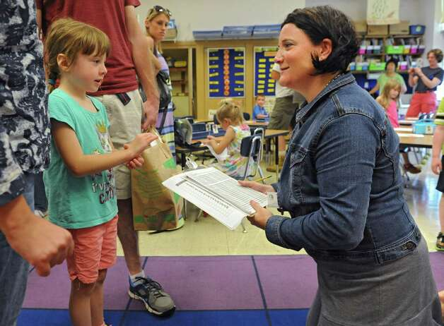 Taylor Arienti, 5, of Wynantskill tells her kindergarten teacher Mrs. Ellen Moak what bus number she will be taking home in the afternoon at Gardner-Dickinson School on Tuesday, Sept. 2, 2014 in North Greenbush, N.Y. Parents brought their kindergarten students to drop off school supplies, meet their teachers and take a quick bus ride. (Lori Van Buren / Times Union) Photo: Lori Van Buren / 00028410A