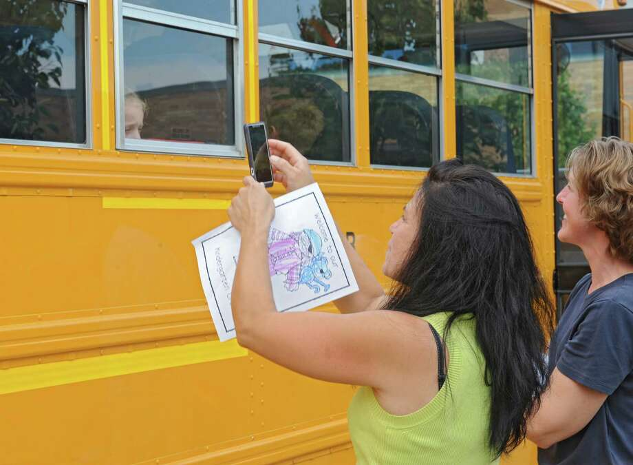 Micheline Geise of Wynantskill takes a photo of her son Lucas Nobre Geise, 5, as kindergarten students take a school bus for a test ride at Gardner-Dickinson School on Tuesday, Sept. 2, 2014 in North Greenbush, N.Y. Parents brought their kindergarten students to drop off school supplies, meet their teachers and take a quick bus ride. (Lori Van Buren / Times Union) Photo: Lori Van Buren / 00028410A