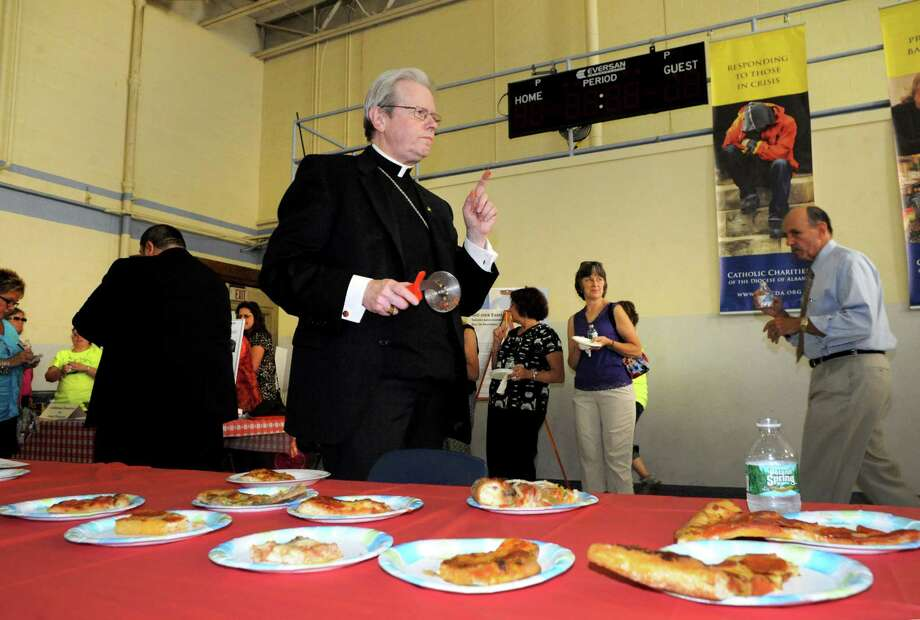"Albany Bishop Edward Scharfenberger trys various offerings from Capital Region pizza makers during the  ""Bishop's Choice"" pizza challenge at the Catholic Charities office on Tuesday Sept. 2, 2014 in Rensselaer, N.Y. The Orchard Tavern was the Bishops Coice winner. Michael P. Farrell/Times Union) Photo: Michael P. Farrell / 00028430A"