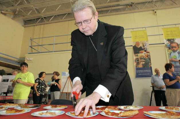 """Albany Bishop Edward Scharfenberger trys various offerings from Capital Region pizza makers during the  """"Bishop's Choice"""" pizza challenge at the Catholic Charities office on Tuesday Sept. 2, 2014 in Rensselaer, N.Y. The Orchard Tavern was the Bishops Coice winner. Michael P. Farrell/Times Union) Photo: Michael P. Farrell / 00028430A"""