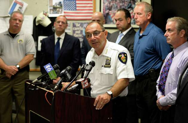 Troy Police Chief John Tedesco is surrounded by the detectives that made arrests in two murder cases as he conducted a press conference giving information on the cases Tuesday morning Sept. 2, 2014 in Troy, N.Y.        (Skip Dickstein/Times Union) Photo: SKIP DICKSTEIN / 00028414A
