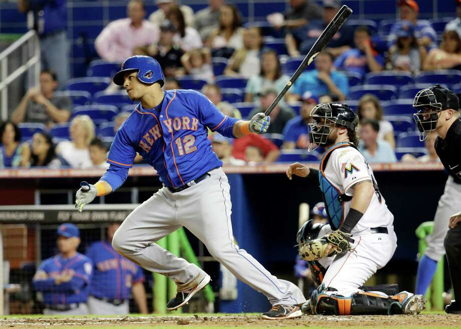 New York Mets' Juan Lagares (12) watches after hitting a RBI singe to score Wilmer Flores in the fourth inning during a baseball game, Tuesday, Sept. 2, 2014, in Miami. At right is Miami Marlins catcher Jarrod Saltalamacchia. (AP Photo/Lynne Sladky) ORG XMIT: FLLS110 Photo: Lynne Sladky / AP