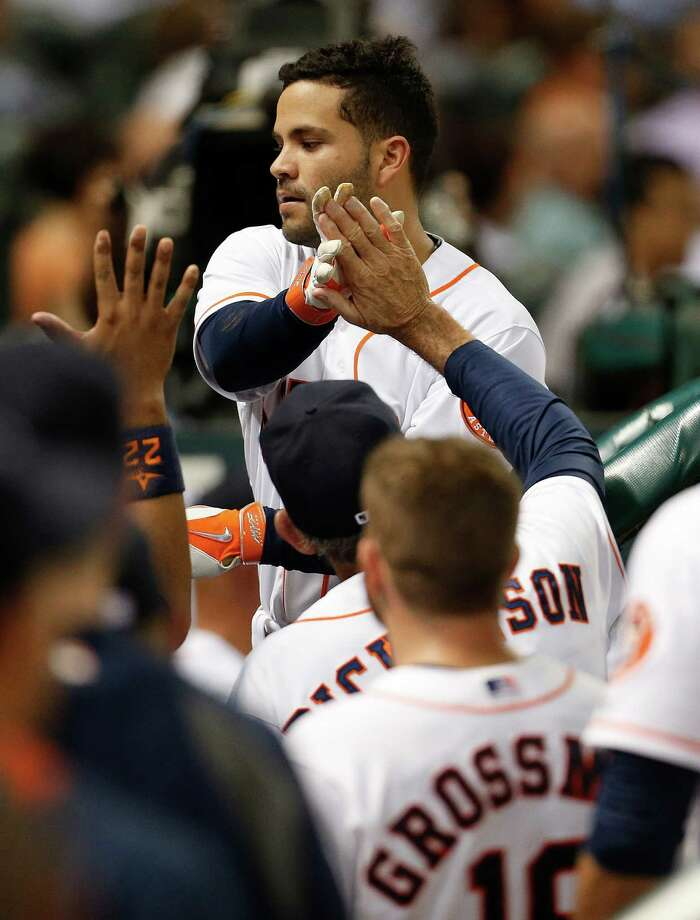 Jose Altuve accepts congratulations on a third-inning homer that was part of another four-hit game for the Astros second baseman. Photo: Karen Warren, Staff / © 2014 Houston Chronicle