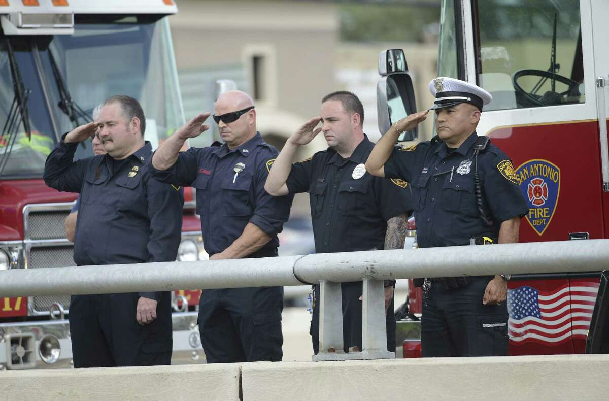 Police officer David Pantoja (right) joins firefighters atop the Henderson Pass overpass as the funeral procession travels north on U.S. 281 on its way to Cornerstone Church.