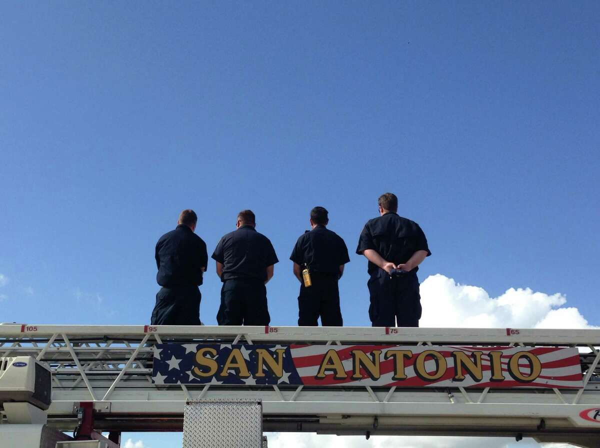 Firefighters stand atop their vehicle at Henderson Pass as they await the procession for Elmendorf police chief Michael Pimental, who was shot and killed on August 23, on Tuesday, Sept. 2, 2014.