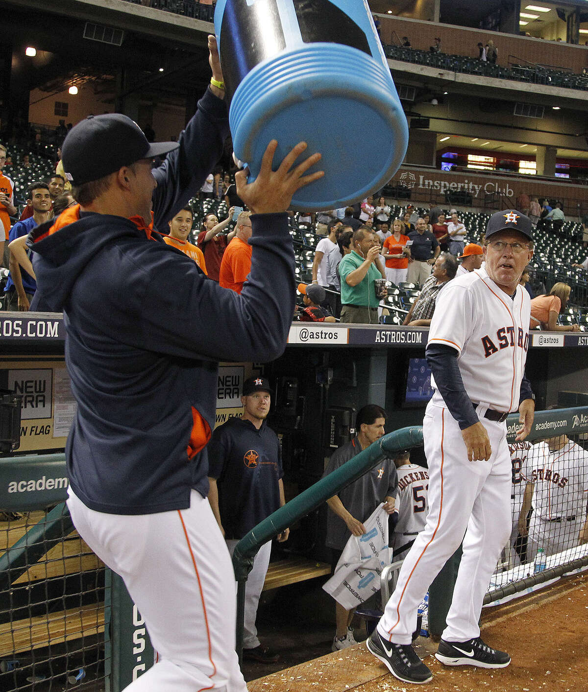Astros interim manager Tom Lawless (right) looks to avoid a celebratory bucket of ice water held by George Springer after Houston won its first game following the firing of Bo Porter.