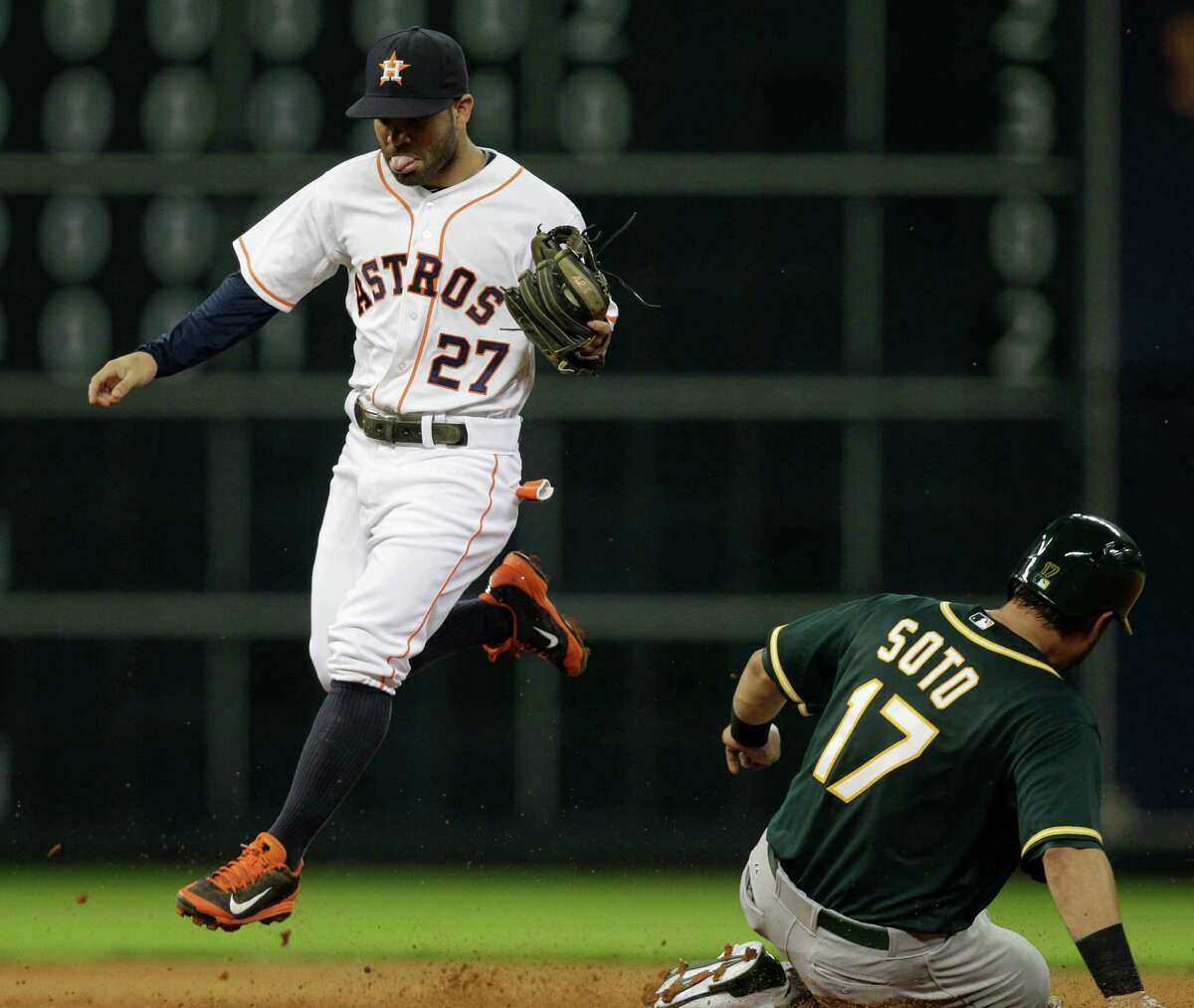 Houston Astros second baseman Jose Altuve leaps after making an out at second base against Oakland Athletics Geovany Soto during the fourth inning at Minute Maid Park Tuesday, Aug. 26, 2014, in Houston. ( Melissa Phillip / Houston Chronicle )