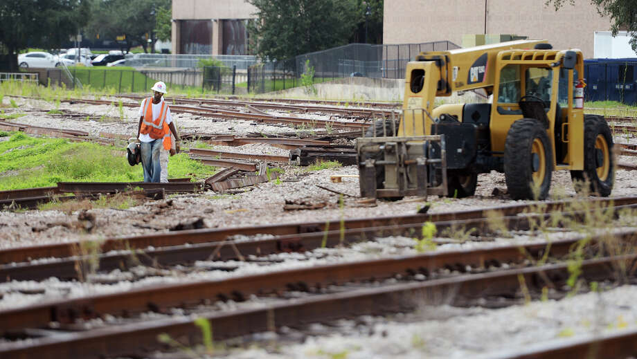 Workers with Trans-Global Solutions, Inc., carry equipment down a track in the north rail interchange yard Tuesday. The Port of Beaumont began demolition of the former north rail interchange yard as part of their Rail Improvement Project on Monday, August 25. Of the six tracks in the small yard, located between downtown and the Neches River, one only line will remain to serve the port. The land formerly taken up by the five tracks will be developed by the City of Beaumont for use by citizens. Photo taken Tuesday 9/2/14 Jake Daniels/@JakeD_in_SETX Photo: Jake Daniels / ©2014 The Beaumont Enterprise/Jake Daniels