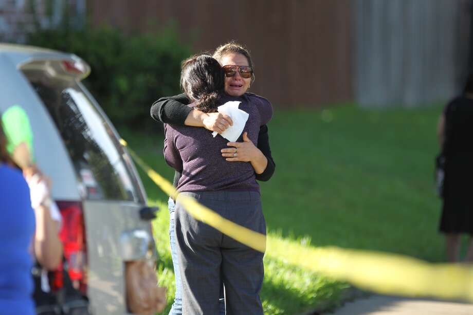 Family and friends console each other at the scene where a 60-year-old woman was hit and killed by a white Ford Expedition at 7:40 a.m. Wednesday in the 8500 block of Neff in Houston. Photo: Gary Coronado, Houston Chronicle / Houston Chronicle