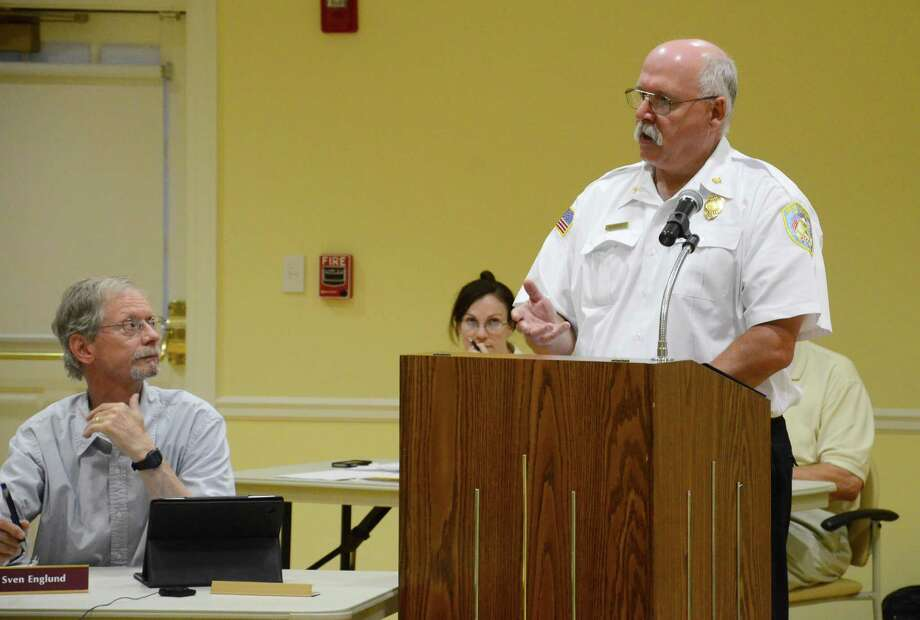 Fire Chief Jack Hennessey, right, speaks about a new interlocal agreement for fire dispatch services with the Westport Fire Department during a Town Council meeting at Lapham Community Center in New Canaan, Conn. Councilman and firefighter Sven Englund, left, supported the new initiative along with other councilmen. Photo: Nelson Oliveira / New Canaan News