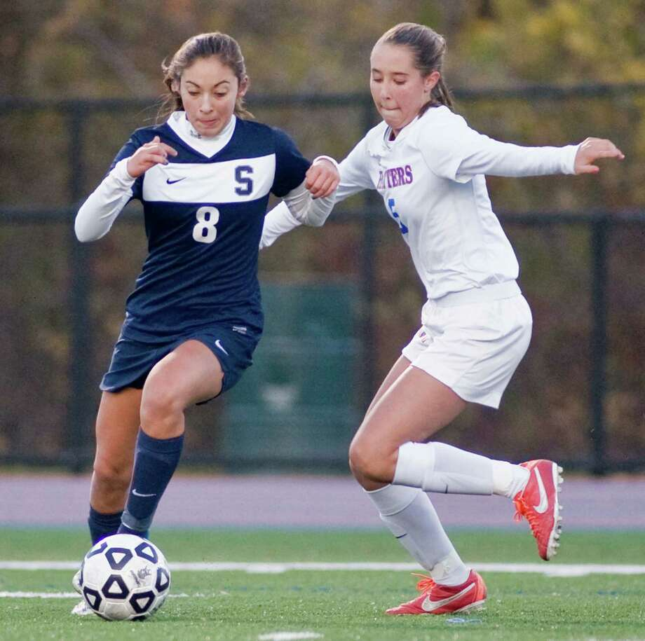 Staples High School's Lauren Garcia tries maneuver the ball away from Danbury High School's Katelyn Mooney in the Class LL state tournament game played at Danbury. Monday, Nov. 4, 2013 Photo: Scott Mullin / The News-Times Freelance
