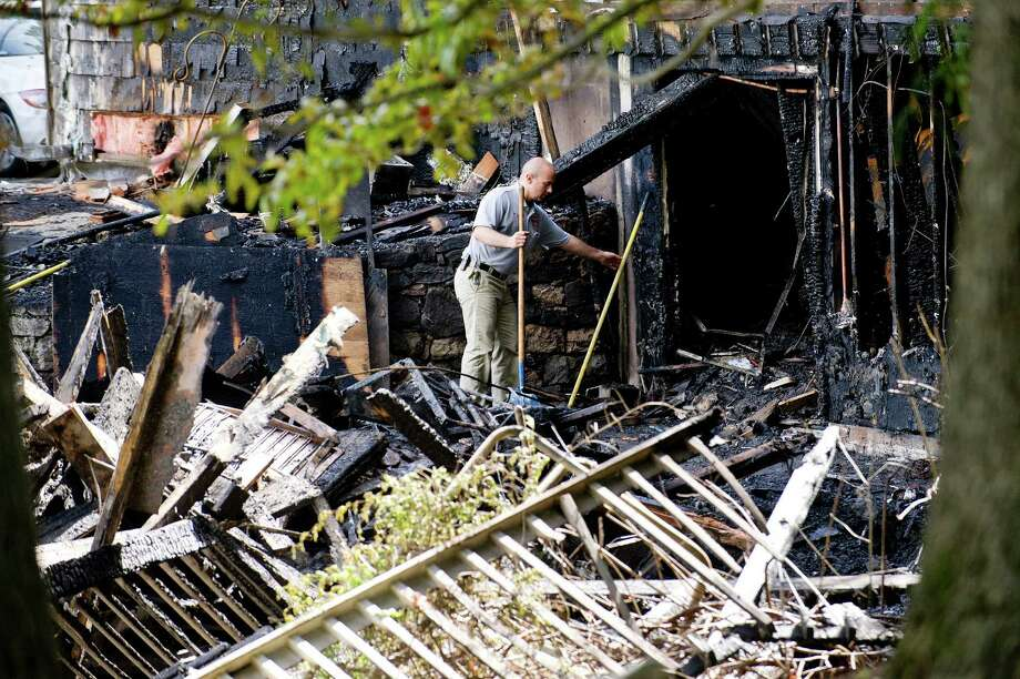 Stamford Fire Department Deputy Fire Marshall Antonio Forte walks on the property at 25 Bittersweet Lane in Stamford, Conn., on Wednesday, September 3, 2014, after a fire early Wednesday morning destroyed the home. Photo: Lindsay Perry / Stamford Advocate