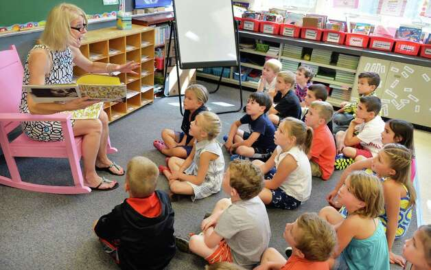 Second grade teacher Mary Beth Goliber, left, reads students on story on the first day back to school at Lake Avenue Elementary School Wednesday Sept. 3, 2014, in Saratoga Springs, NY.  (John Carl D'Annibale / Times Union) Photo: John Carl D'Annibale / 00028428A