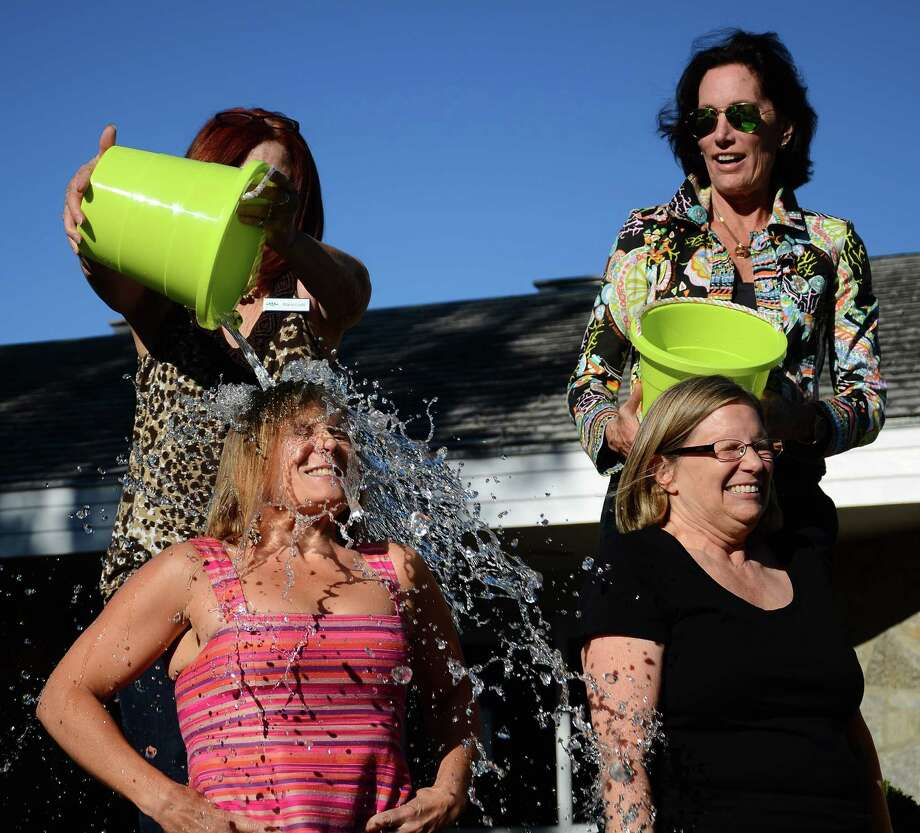 Maria Livoti dumps a bucket of ice water on New Canaan Library's Executive Director Lisa Oldham as part of the ALS Ice Bucket Challenge Friday, Aug. 29, 2014, outside the library in New Canaan, Conn. Several library employees, including Cathy Townsend, bottom right, and former circulation librarian Ann Depuy, top right, joined the challenge that afternoon. Photo: Nelson Oliveira / New Canaan News