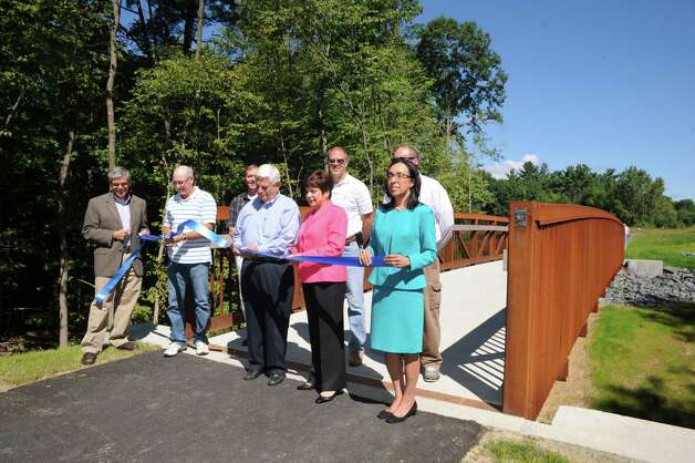 Town of Colonie Supervisor Paula Mahan and Ken Raymond of Prime Companies, center, are joined by other town officials cutting a ribbon for a new portion of the Mohawk-Hudson Bike-Hike Path at Colonie Town Park on Friday Aug. 29, 2014 in Colnie, N.Y. (Michael P. Farrell/Times Union) Photo: Michael P. Farrell, Albany Times Union / 00028388A