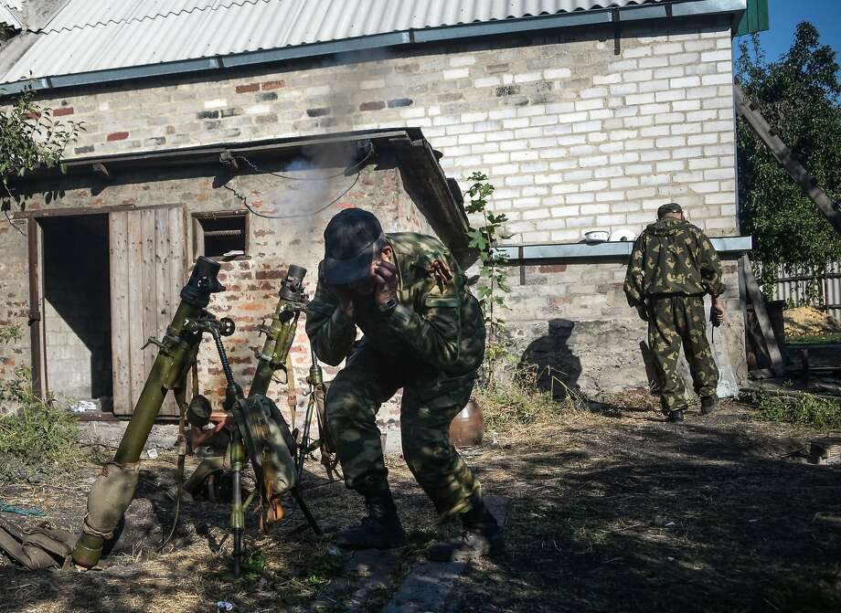 "Pro-Russian rebels fire at Ukrainian army positions during shelling in Donetsk in eastern Ukraine. Russian President Vladimir Putin called on insurgents to ""stop advancing"" and urged Ukraine to withdraw its troops from the region. Photo: Mstyslav Chernov, Associated Press"