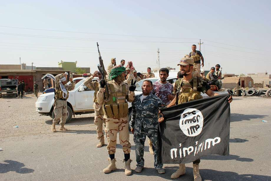 In this Monday, Sept. 1, 2014 photo, Shiite militiamen hold the flag of the Islamic State group they captured, during an operation outside Amirli, some 105 miles (170 kilometers) north of Baghdad, Iraq. Under the shadow of the Islamic State group threat, governments from France to Indonesia are moving aggressively to block would-be jihadis from taking their fight to Syria and Iraq. New laws make it easier to seize passports. Suspected fighters are being plucked from planes. Authorities are blocking finances and shutting down radical mosques. Behind the scenes, Western intelligence agencies are striving to stay ahead of tech-savvy radicalized Muslims by pressuring Silicon Valley firms to wipe extremist content from websites and toying with new technologies to identify returning fighters at the border. Britain has taken a particularly active role in censoring content deemed to break the country's strict rules against extremist propaganda. U.K. officials recently revealed it had been granted ?super flagger? status on sites such as YouTube, meaning their requests to remove videos with grisly content or that encourage terrorism are fast-tracked. (AP Photo) Photo: Associated Press
