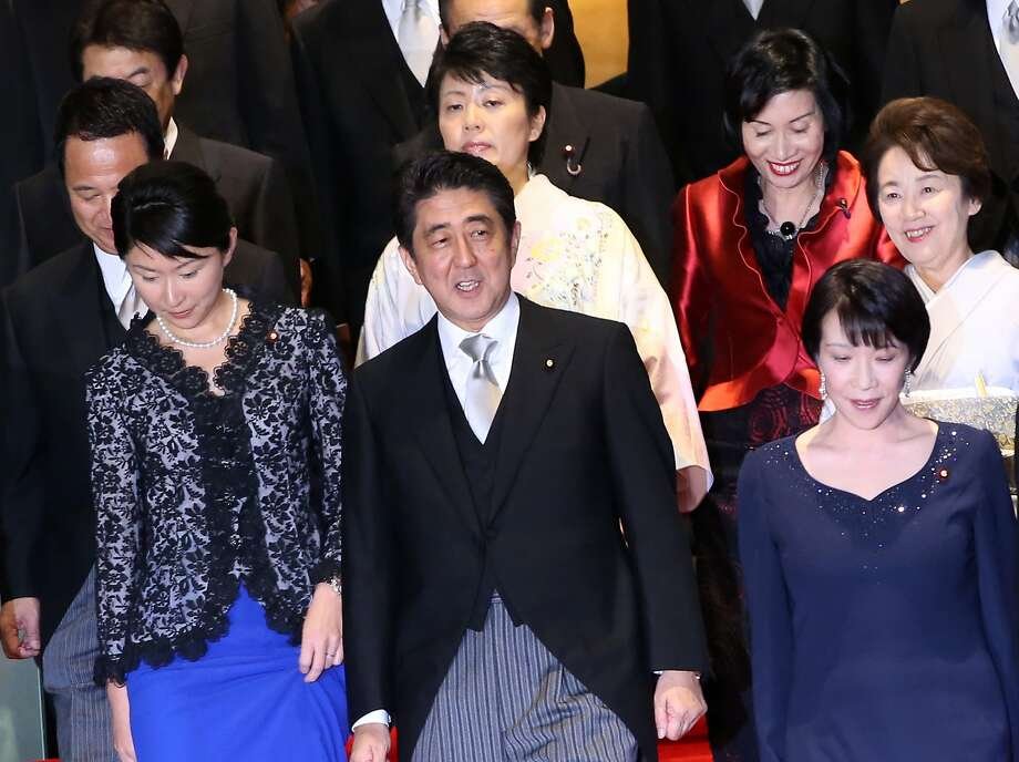 Prime Minister Shinzo Abe, front row center, and his new Cabinet walk for a photo session in Tokyo. Photo: Eugene Hoshiko, Associated Press