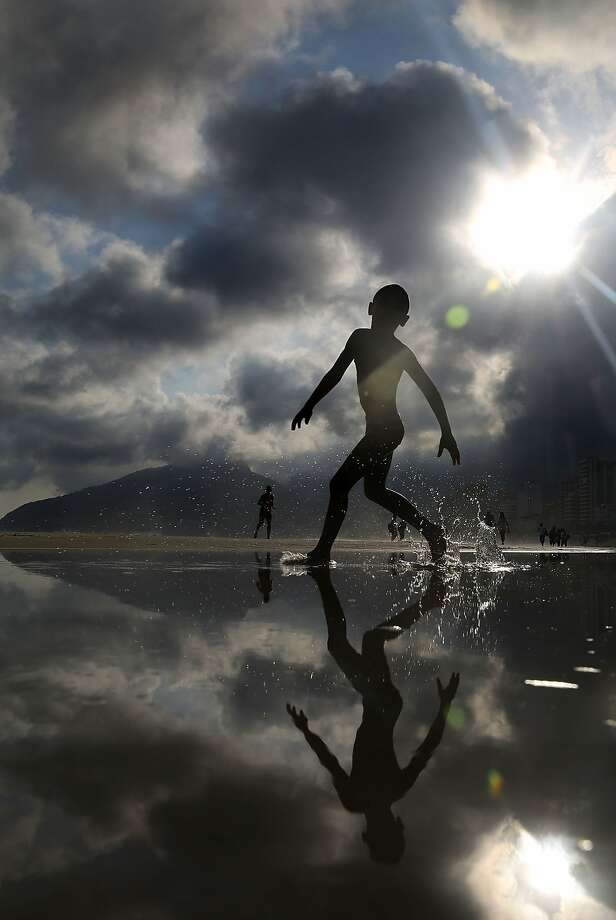 The boy from Ipanema: A youngster runs through the water on Ipanema beach in Rio de Janeiro. Photo: Mario Tama, Getty Images