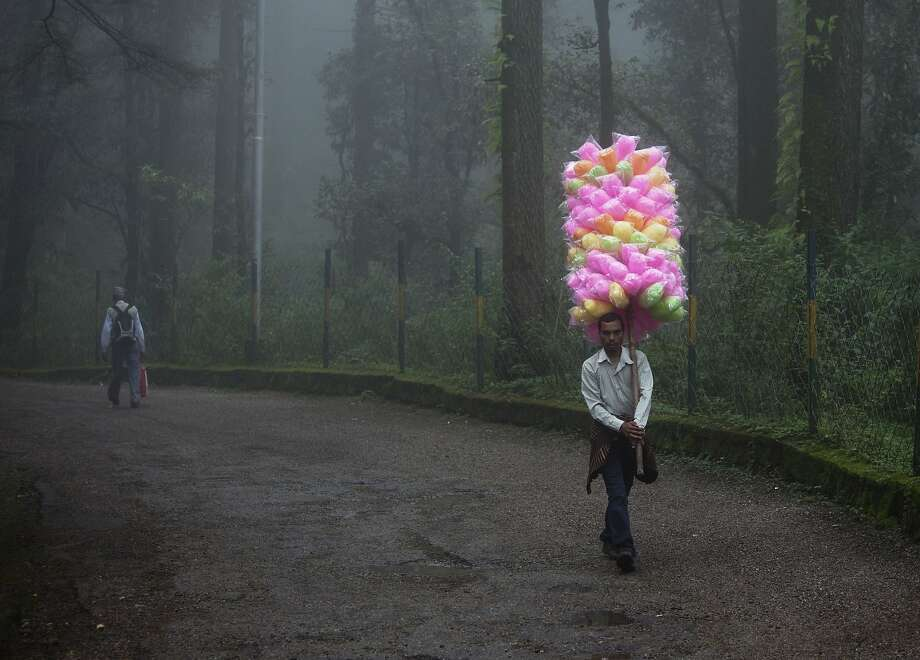 Cotton  candy! Get your cotton candy! In Dharmsala, India, you can find candy vendors in the strangest places. Like a spooky, damp forest, for instance. Photo: Ashwini Bhatia, Associated Press