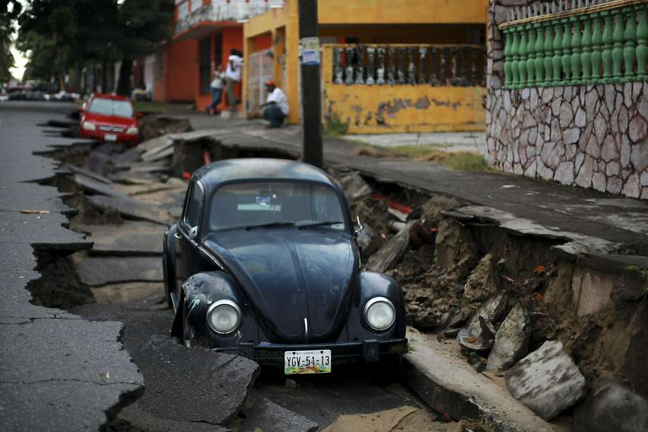 Street swallows Bug: A VW and another car lie in a caved-in street in Veracruz, Mexico, after heavy rains inundated the Gulf port. Mexico's Gulf states were bracing for more bad weather as Tropical Storm Dolly crosses the coast. Photo: Felix Marquez, Associated Press