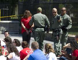 Demonstrators are arrested outside the White House in Washington on Thursday, Aug. 28, 2014 during a rally calling for President Barack Obama to stop deportations of migrants in the country illegally and to make a decision on how to provide relief for immigrant families. U.S. Park Police said 145 people were arrested. (AP Photo/Jose Luis Magana)