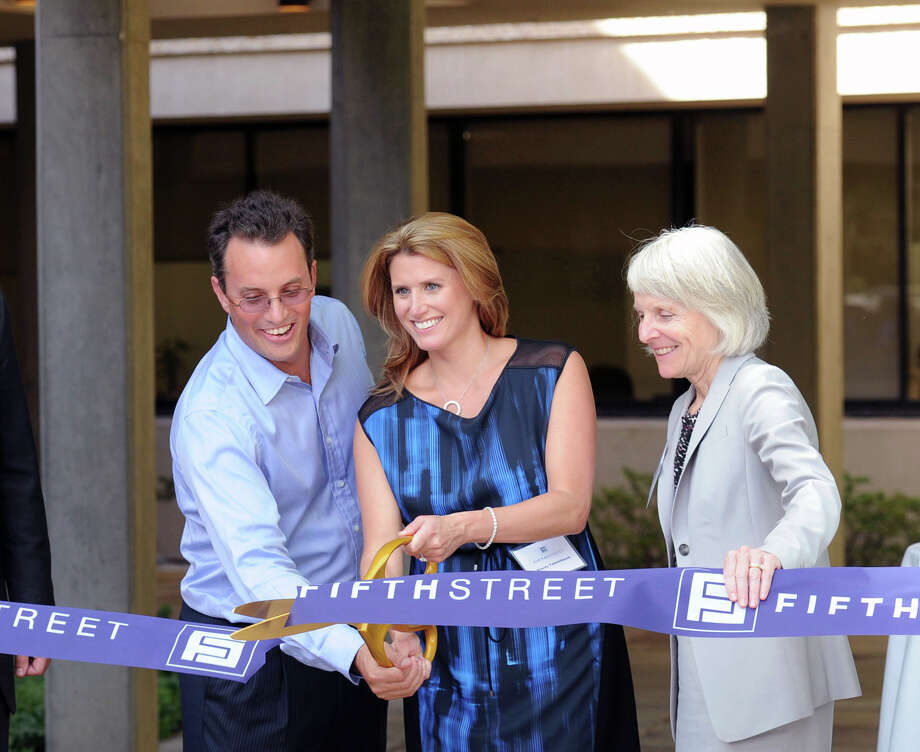 At left, Leonard Tannenbaum, the chief executive officer of Fifth Street Management, and his wife, Stacey, center, cut the ribbon during the ceremony commemorating the formal opening of Fifth Street's new office building at 777 West Putnam Ave., Greenwich, Conn., Wednesday, Sept. 3, 2014. At right is the Commissioner of the Connecticut Department of Economic and Community Development, Catherine Smith. Photo: Bob Luckey / Greenwich Time