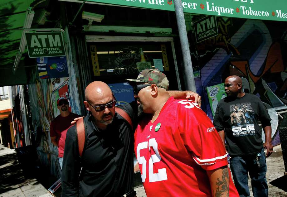 Elwood MacMurray, right, an uncle of Rashawn Williams, 14, gets a hug from Roberto Vargas, a community leader whose kids went to school with Rashawn, in front of the market where he was fatally stabbed in the Mission District on Tuesday evening, in San Francisco, Calif., on Wednesday, September 3, 2014. Photo: Sarah Rice / Special To The Chronicle / ONLINE_YES