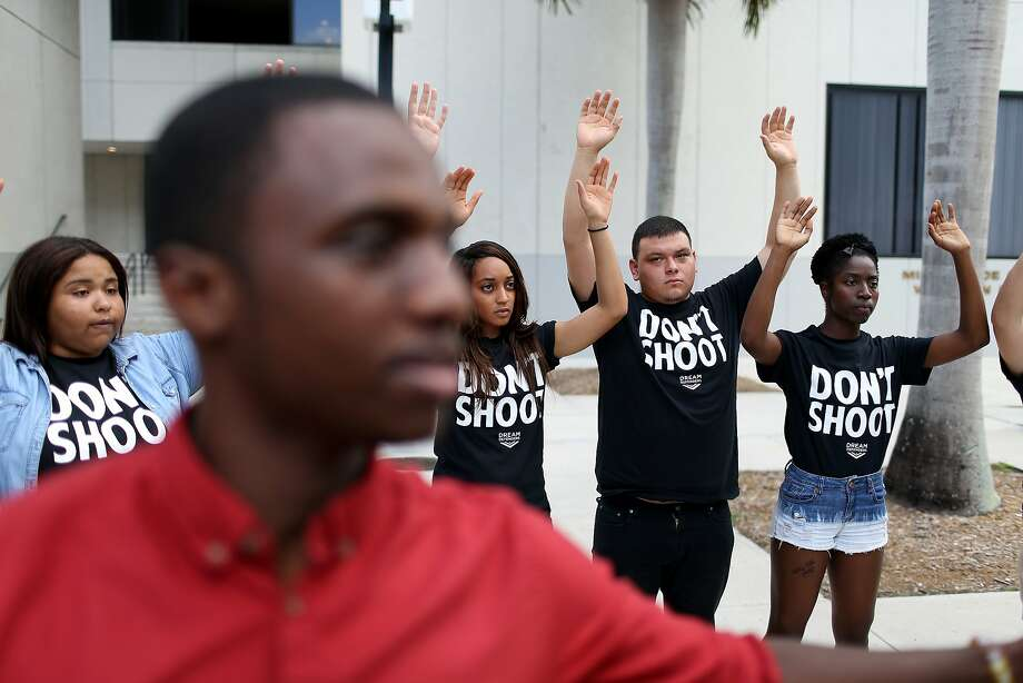 "Protesters shout ""hands up, don't shoot"" outside a federal building in Miami. The protesters want justice for 17-year old graffiti artist Israel Hernandez, killed by a Taser shock from a Miami Beach police officer. Photo: Joe Raedle, Getty Images"