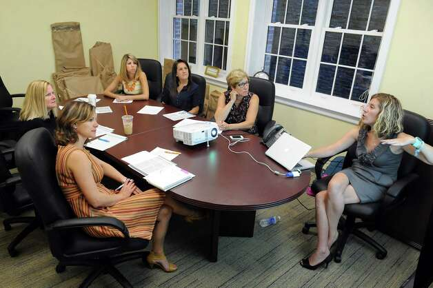 Amanda Wheeler of CornerStone Telephone, right, trains Rensselaer County Regional Chamber of Commerce employees on a new phone system in the second floor conference room on Wednesday, Sept. 3, 2014, at the Proctor Building in Troy, N.Y. (Cindy Schultz / Times Union) Photo: Cindy Schultz / 00028431A