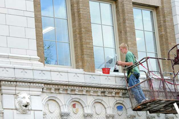 Evan Remillard of Jewitt Restoration works on the glazing on the Proctor Building on Wednesday, Sept. 3, 2014, in Troy, N.Y. (Cindy Schultz / Times Union) Photo: Cindy Schultz / 00028431A