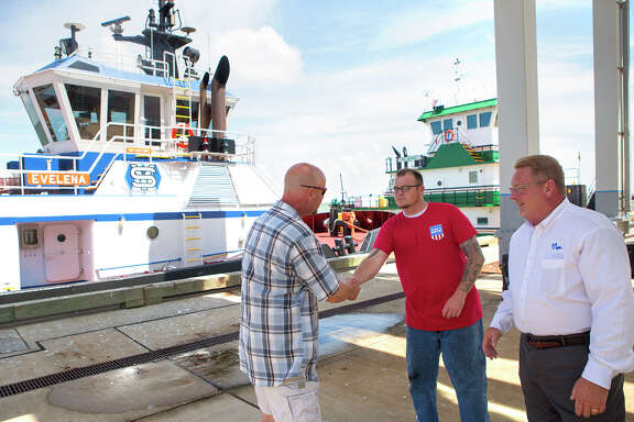 Army veteran John Cowan, left, shakes hands with G & H Towing Company Engineer Project Manager, Jason Dewitt, center, and Port Captain Russell Gibson, right, during a job fair hosted by The American Maritime Partnership at the Bayport Cruise Terminal, Wednesday, Sept. 3, 2014, in Pasadena. The fair is designed for ex-military to interview for maritime jobs. (Cody Duty / Houston Chronicle)