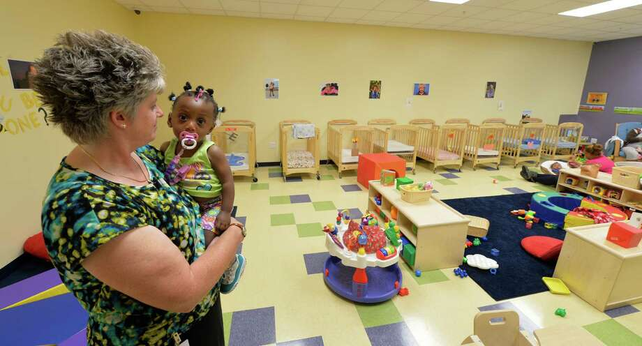 Karen Seyboth, director holds Tahjaye Randolph on the Grand Opening Day of the Early Childhood Center Wednesday Sept. 3, 2014 in Albany, N.Y.   (Skip Dickstein/Times Union) Photo: SKIP DICKSTEIN / 00028433A