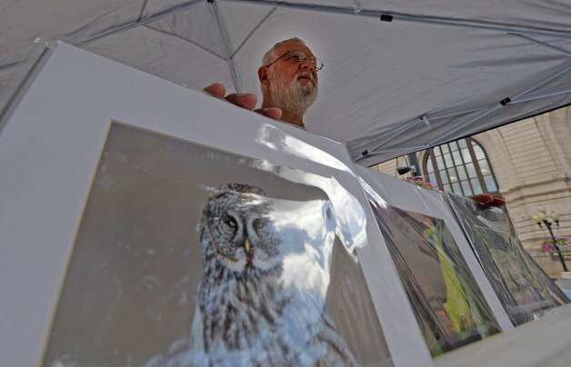 Fine art wild animal photographer Dennis Donohue shows off his images at the art fair in Tricentennial Park Wednesday afternoon Sept. 3, 2014 in Albany, N.Y.  The Artfair will continue every Wednesday during the month of September.    (Skip Dickstein/Times Union) Photo: SKIP DICKSTEIN / 00028200A