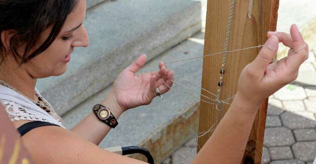 Casey DePoalo works on one of her hemp jewelry pieces at the art fair in Tricentennial Park Wednesday afternoon Sept. 3, 2014 in Albany, N.Y.  The Artfair will continue every Wednesday during the month of September.    (Skip Dickstein/Times Union) Photo: SKIP DICKSTEIN / 00028200A
