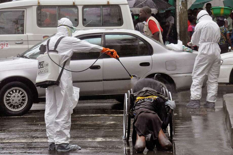 Health workers spray the body of a amputee suspected of dying from the Ebola virus with disinfectant, in a busy street in Monrovia, Liberia, Tuesday, Sept. 2, 2014.  Food in countries hit by Ebola is getting more expensive and will become scarcer because many farmers won't be able to access fields, a U.N. food agency warned Tuesday. An Ebola outbreak in West Africa has killed more than 1,500 people, and authorities have cordoned off entire towns in an effort to halt the virus' spread.  (AP Photo/Abbas Dulleh) ORG XMIT: ALIB101 Photo: Abbas Dulleh / AP