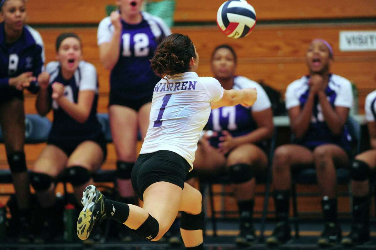 Lauren Jarrell of Warren dives to save the ball during District 27-6A volleyball action against O'Connor at the Paul Taylor Fieldhouse on Wednesday, Sept. 3, 2014.
