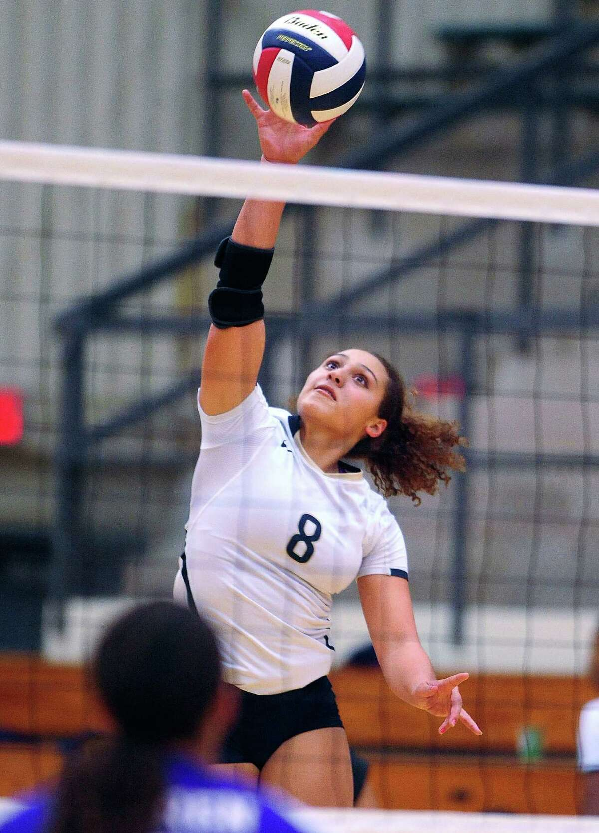 Gilliane Simpkins (8) of O'Connor High School tips the ball over the net during District 27-6A volleyball action against Warren at the Paul Taylor Fieldhouse on Wednesday, Sept. 3, 2014.
