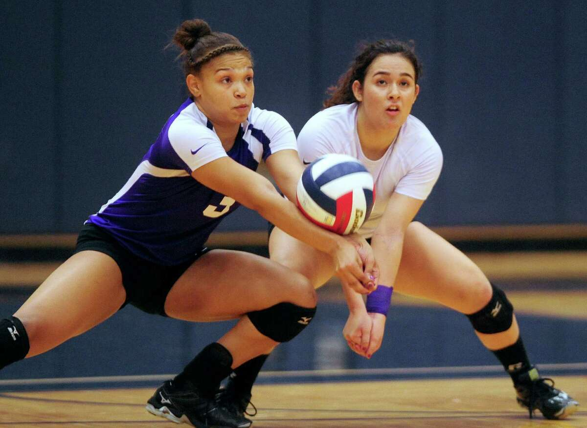 Brittany Lawson, left, and Lauren Jarrell of Warren return a ball during District 27-6A volleyball action against O'Connor at the Paul Taylor Fieldhouse on Wednesday, Sept. 3, 2014.
