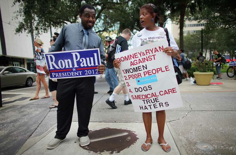Ron Paul supporter Darrell Young debates with Tonya Wieman, a backer of President Barack Obama, outside the Republican National Convention in Tampa, Fla., in August 2012. Photo: Getty Images File Photo / 2012 Getty Images