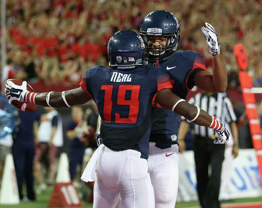 Arizona's Davonte' Neal (19) celebrates with Austin Hill after catching a 13-yard TD pass in a 58-13 rout of UNLV on Friday. Neal caught two passes for 29 yards, while Hill had three catches for 110 yards and a score. Photo: Christian Petersen / Getty Images / 2014 Getty Images