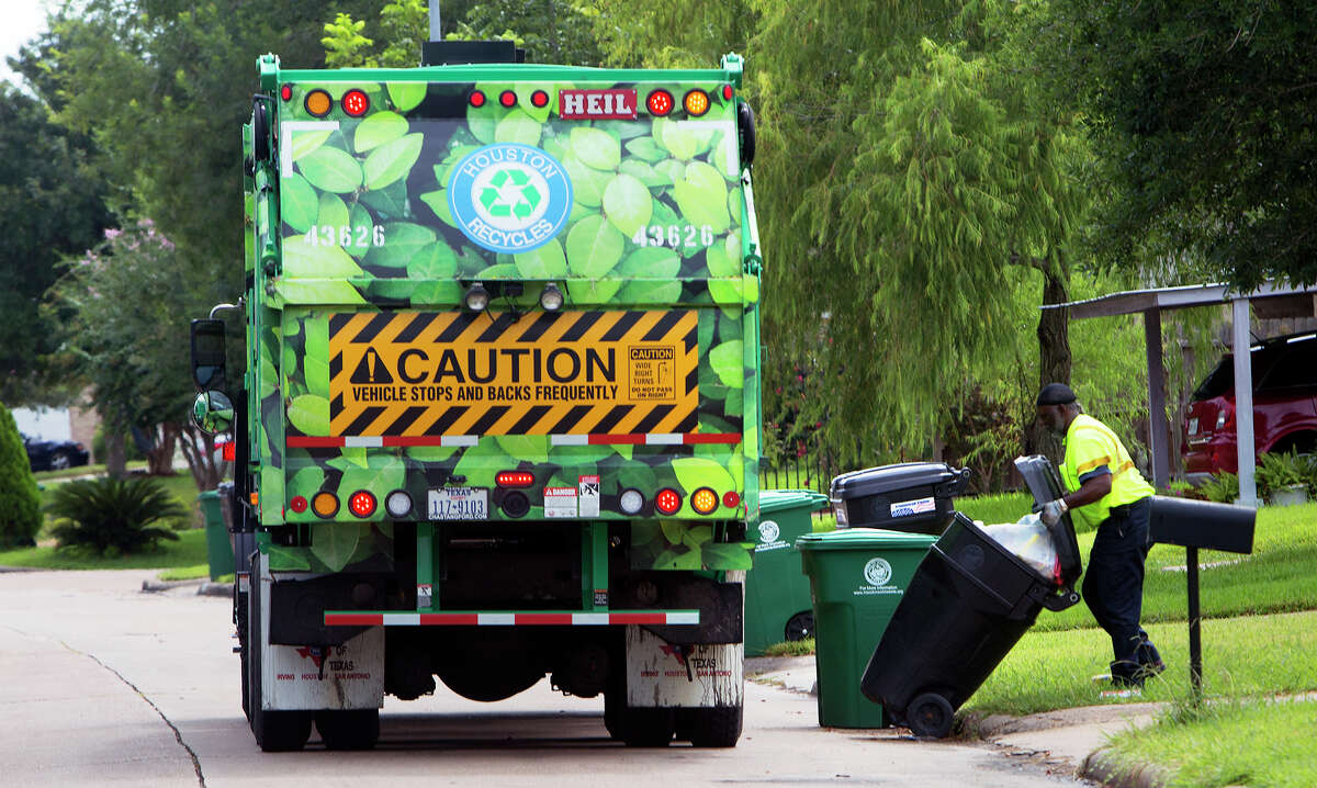 Ed Robinson picks up a trash bin after knocking it over along Windy Royal Drive, Friday, Aug. 29, 2014, in Houston.