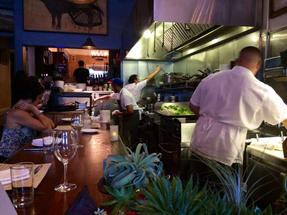 The open kitchen is surrounded by a dining counter at Blue Plate in the Mission.