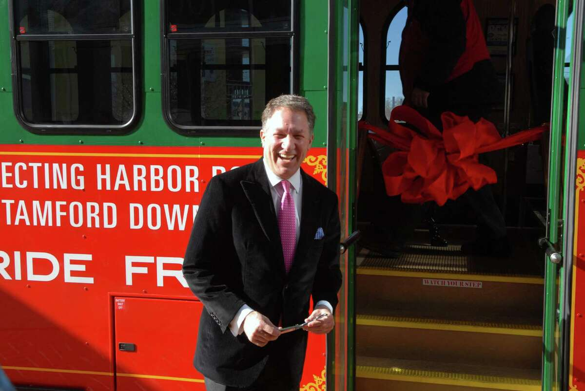 Carl Kuehner, Building and Land Technology's Chief Executive Officer, gets ready to cut the ribbon for the inaugural ride on the Harbor Point Trolley in Stamford, Conn. on Friday February 14, 2014.