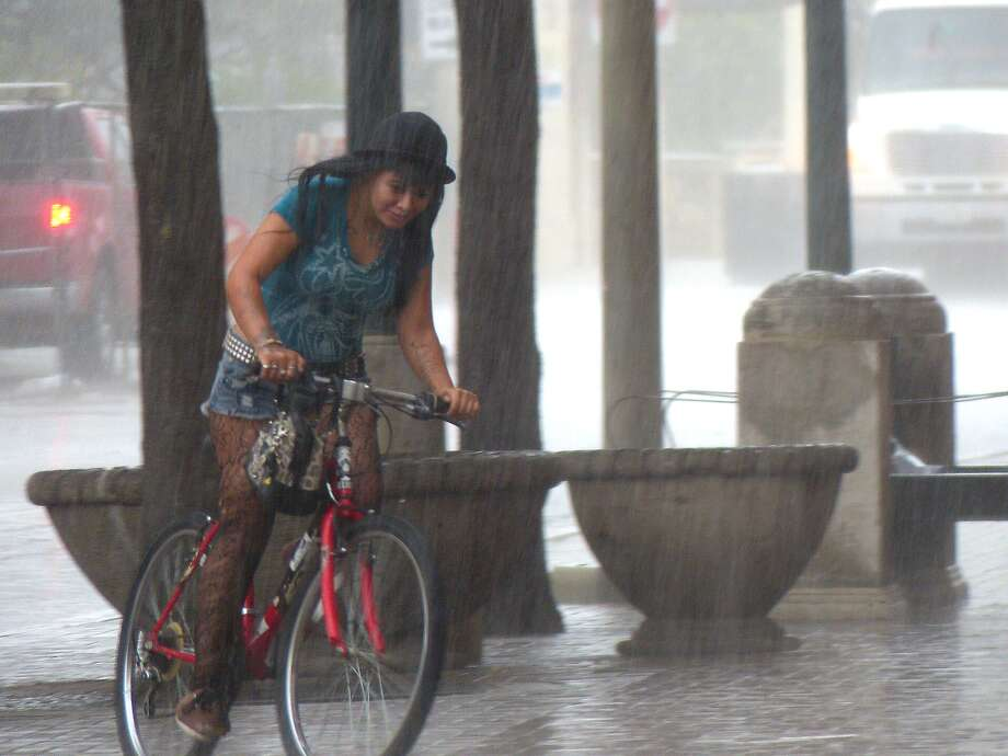 A young woman rides her bicycle along Alamo Street during a rain shower in San Antonio on Thursday, September 4, 2014. Photo: Billy Calzada, San Antonio Express-News /  San Antonio Express-News
